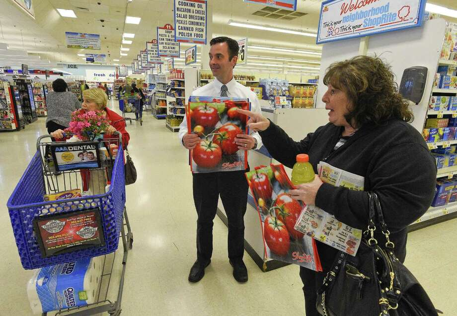 Dominick Cingari, center, hands out free reusable bags on April. 27, 2018 to customers like Josephine Colangelo of Port Chester, New York, at right, who travels to the ShopRite Market regularly on Stamford' Westside. The store, one of 11 owned and operated by the  owned the Cingari family seeks to spur shoppers to bring their own reusable bags as Board of Representatives look to draft an ordinance that would prohibit the use of non-recyclable plastic bags. Photo: Matthew Brown / Hearst Connecticut Media / Stamford Advocate