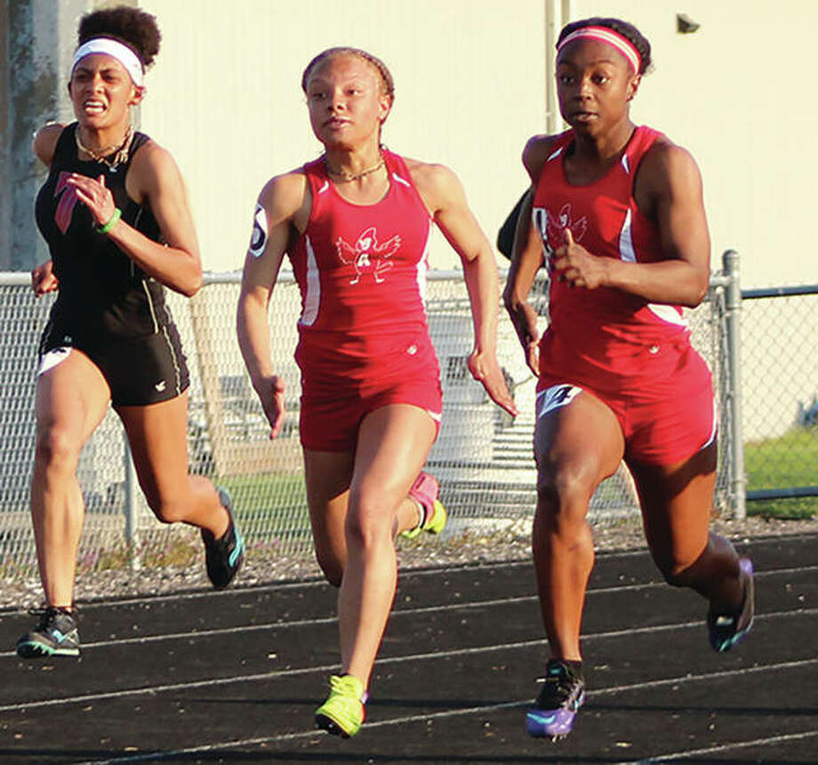 Alton's Jeanea Epps (right) and Rashia Johnson (middle) take a lead on Triad's Elizabeth Jones Smith during the 100 meters Tuesday at the Madison County Meet in Highland. Epps came back Friday to win the 100 and 200 meters and joined Johnson on the 4x100 relay that helped the Redbirds to a third-place finish at the Collinsville Invite. Photo:       Greg Shashack / The Telegraph