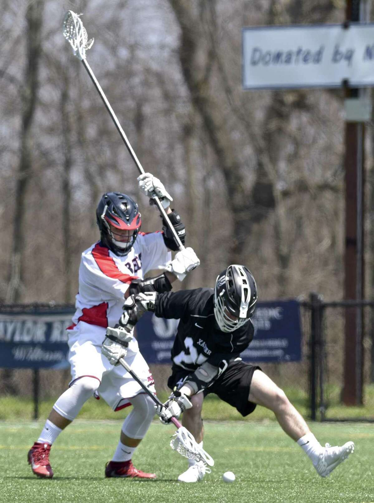 new Fairfield's Zachary Buffington (4) and Xavier's Justin Prete (27) fight for the ball in the boys lacrosse game between Xavier and New Fairfield high schools, Saturday, April 28, 2018, at New Fairfield High School, New Fairfield, Conn.
