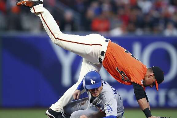 Los Angeles Dodgers' Cody Bellinger breaks up a double play as San Francisco Giants second baseman Joe Panik falls on top of him in the second inning of a baseball game Friday, April 27, 2018, in San Francisco. Yasiel Puig was safe at first base. (AP Photo/Ben Margot)
