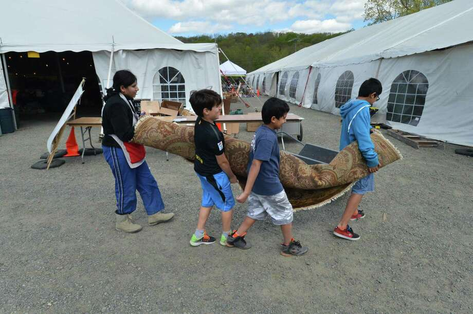 At the 2017 Minks to Sinks spring sale, an oriental carpet is carried to the tent by volunteer Sadiqua Ali and her sons Afroz and Faizaan with friend Pamir Canan in Wilton. Photo: Alex Von Kleydorff / Hearst Connecticut Media / Norwalk Hour