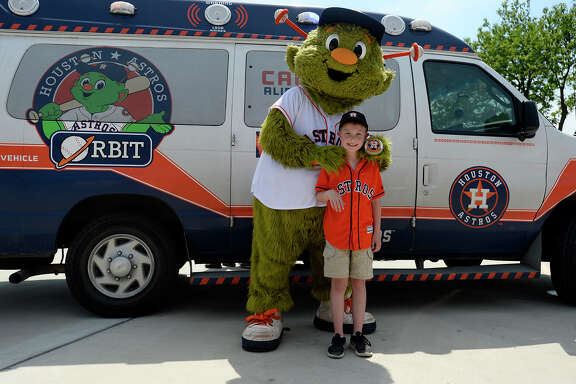 Weston Sasser, 9, with Houston Astros mascot Orbit during the Astros Shuttle Crew's visit to a Neches Federal Credit Union branch in Port Neches. Sasser's family home was destroyed by Tropical Storm Harvey, and he is decorating his rebuilt bedroom with an Astros theme.  Photo taken Saturday 4/28/18 Ryan Pelham/The Enterprise