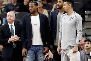 FILE - In this Jan. 21, 2018, file photo, San Antonio Spurs guard Danny Green, right, stands at the bench with injured teammates Kawhi Leonard, second from left, and Rudy Gay, center, during the second half of an NBA basketball game against the Indiana Pacers in San Antonio. The absolute unwillingness to answer certain questions is part of the San Antonio Spurs' mystique. The Spurs just don't share much. So there is some unmistakable irony here that when it comes to the obviously fractured relationship between San Antonio and Kawhi Leonard, it's the Spurs who are the ones frustrated by the lack of answers. (AP Photo/Eric Gay, File)