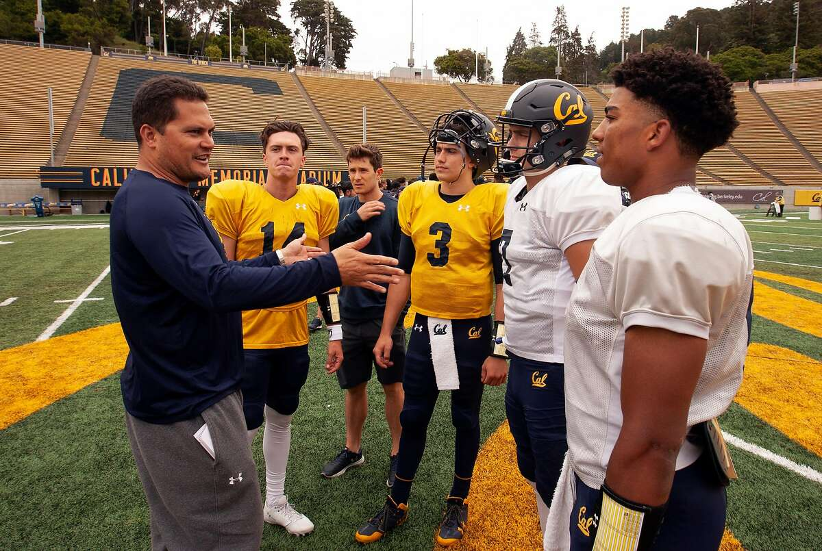 California quarterback coach Marques Tuiasosopo, left, talks to his QBs following the spring football scrimmage at Memorial Stadium, Saturday, April 28, 2018 in Berkeley, Calif. The quarterbacks are, from left, Chase Forrest (14), Ross Bowers (3), Chase Garber (7) and Brandon McIlwain. Man third from left is unidentified.