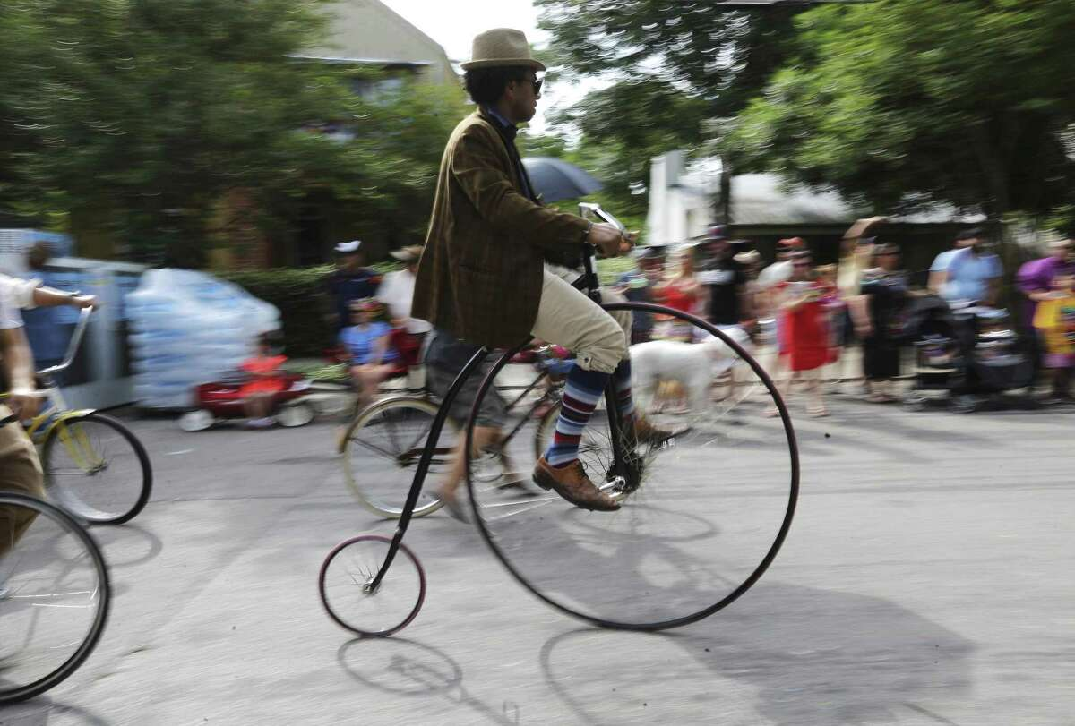 Tito Bradshaw rides a penny-farthing bicycle as the King William Fair kicks off with its ever-quirky parade in the streets of the historic district, April 28, 2018.