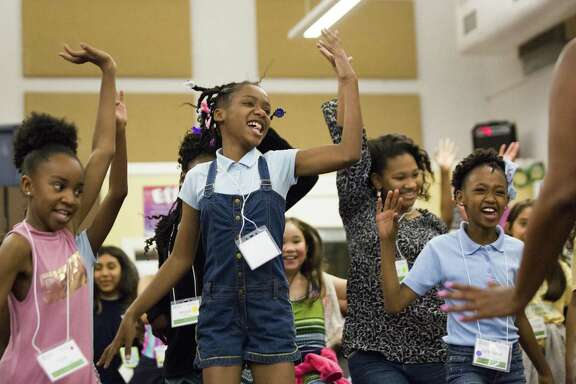 Jordan Gaines, center, learns about West African traditional dances that are part of the rituals celebrating the coming of age. The session took place Saturday at the We Are Girls Houston Conference, designed especially for girls in grades 3-8.
