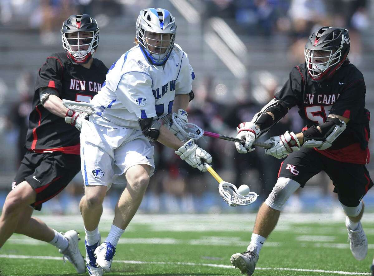 Darien's Tanner Strub (40) passes the ball on the opening face off against New Canaan's Charlie Borthwick (37) and Nicholas Crovatto (55) in a FCIAC boys lacrosse game in Darien, Conn. on April. 28, 2018. Darien defeated New Canaan 9-7.