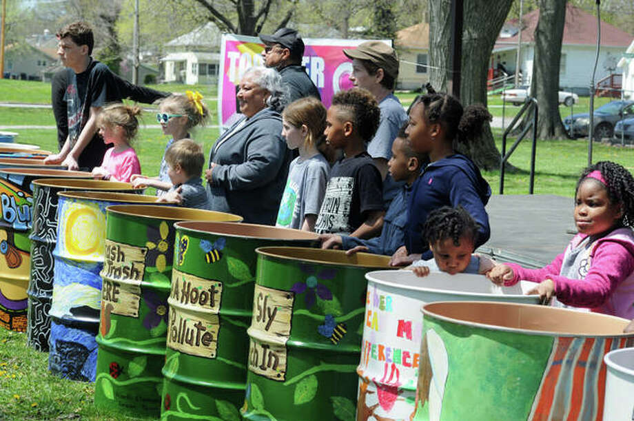 Students, teachers and organizers proudly display the new decorated trash cans at Killion Park. Photo:       David Blanchette | For The Telegraph