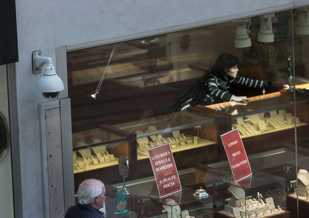 A salesperson at a jewelery story seen through it's store front with a Union Square District CCTV PTZ camera mounted at left on Wednesday, April 25, 2018 in San Francisco, CA.