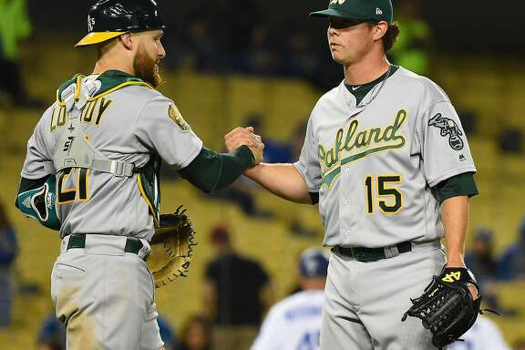 LOS ANGELES, CA - APRIL 11:  Jonathan Lucroy #21 of the Oakland Athletics shakes hands with Emilio Pagan #15 of the Oakland Athletics who earned a save in the game against the Los Angeles Dodgers at Dodger Stadium on April 11, 2018 in Los Angeles, California.  (Photo by Jayne Kamin-Oncea/Getty Images)