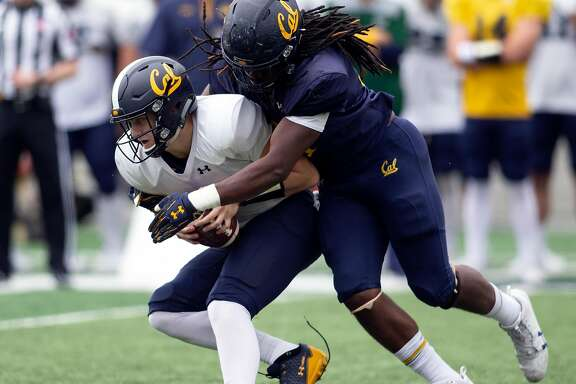 California quarterback Chase Garbers, left, ducks away from the tackle of linebacker Alex Funches during the spring football scrimmage at Memorial Stadium, Saturday, April 28, 2018 in Berkeley, Calif.