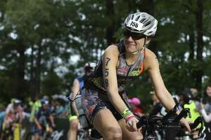 Heidi Brewer smiles at her supporters while biking in the 2018 Memorial Hermann IRONMAN® North American Championship Texas Triathlon on Saturday, April 28, 2018, in The Woodlands. The IRONMAN features 2.4 miles of swimming, 112 miles of biking and 26.2 miles of running. ( Yi-Chin Lee / Houston Chronicle )