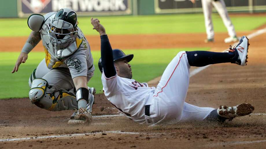 Houston Astros second baseman Jose Altuve (27) is safe at home under Oakland Athletics catcher Bruce Maxwell (13) after a sacrifice fly by Josh Reddick (22) in the first inning. Houston Astros host the Oakland A's at Minute Maid Park on Saturday, April 28, 2018, in Houston. Astros are behind in the series 1-0. Photo: Elizabeth Conley, Houston Chronicle / © 2018 Houston Chronicle