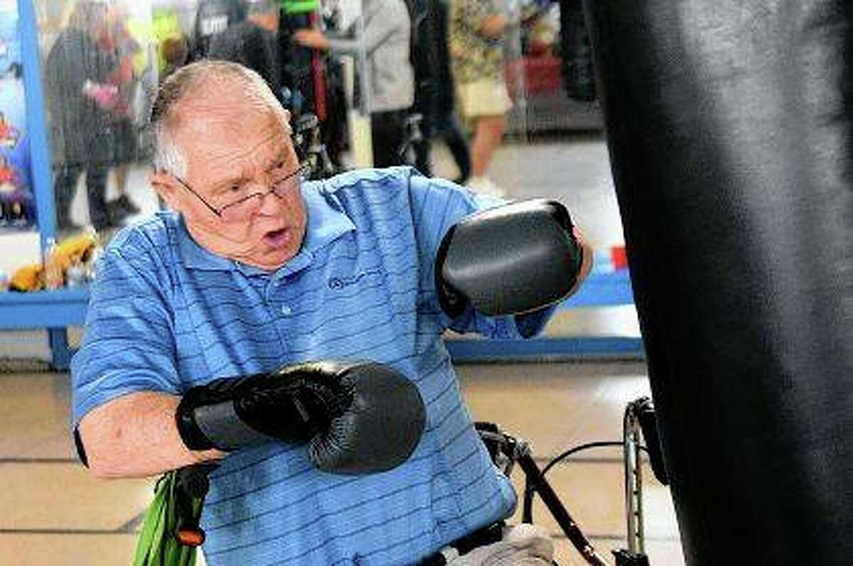 Bill Wise hits the bag during a workout with Rock Steady Boxing at the Weinberg Arcade in Galesburg. The class helps build strength, coordination and balance for people with Parkinson's disease.