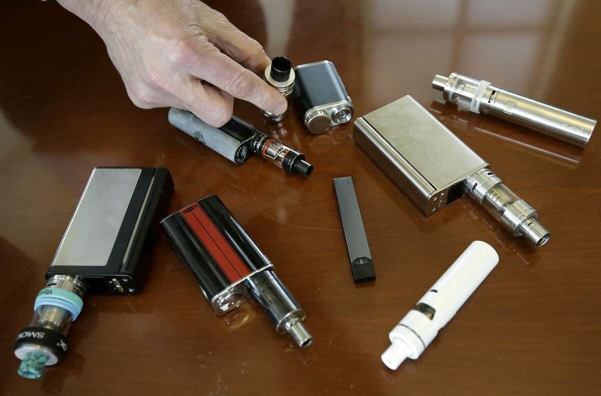 In this Tuesday, April 10, 2018 photo Marshfield High School Principal Robert Keuther displays vaping devices that were confiscated from students in such places as restrooms or hallways at the school in Marshfield, Mass. Health and education officials across the country are raising alarms over wide underage use of e-cigarettes and other vaping products. The devices heat liquid into an inhalable vapor that's sold in sugary flavors like mango and mint, and often with the addictive drug nicotine. (AP Photo/Steven Senne)