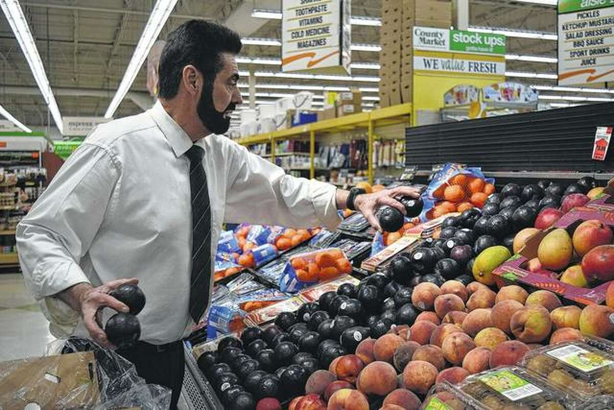 Pat Durcan, produce manager at County Market, restocks plums in the produce section.