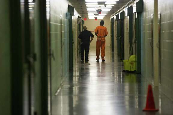 An inmate is escorted down a hallway in the Harris County jail, Thursday, March 29, 2018, in Houston.  ( Mark Mulligan / Houston Chronicle )