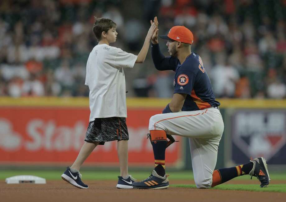 """Austin Helmers, 11, high-fives Houston Astros shortstop Carlos Correa (1) during the """"Kids Take the Field"""" event before the Houston Astros take on the Oakland A's at Minute Maid Park for the third of a three-game series on Sunday, April 29, 2018, in Houston. Photo: Elizabeth Conley, Houston Chronicle / © 2018 Houston Chronicle"""