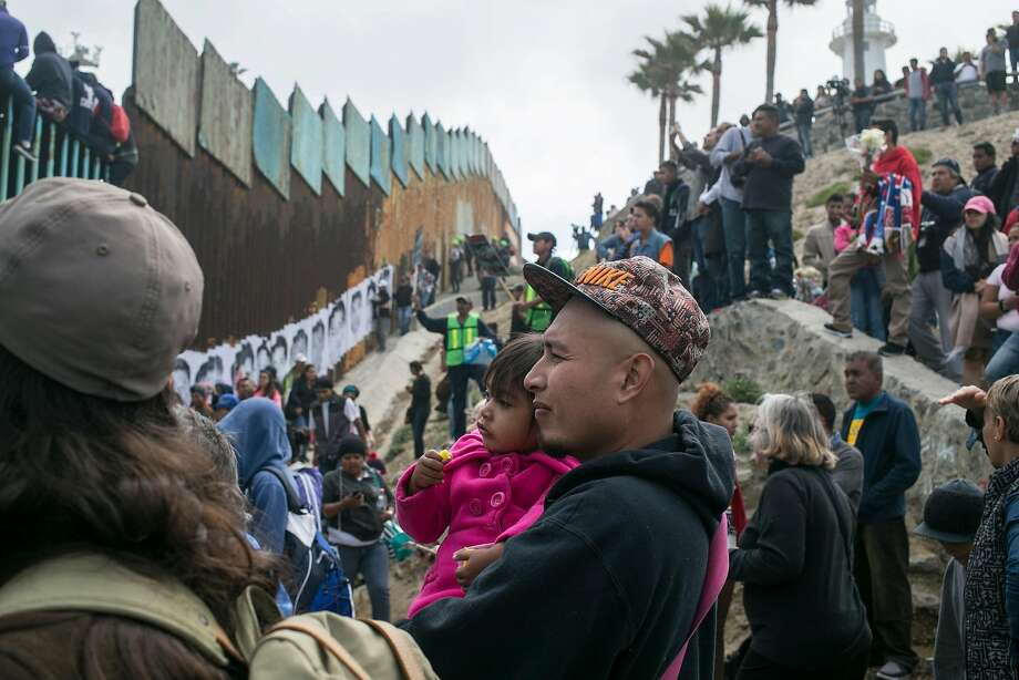 Hundreds of migrants from Central America who traveled as a caravan en masse through Mexico gather with supporters at the border wall with the U.S., where it ends at the Pacific Ocean, in Tijuana, Mexico April 29, 2018.  Photo: Meghan Dhaliwal / New York Times