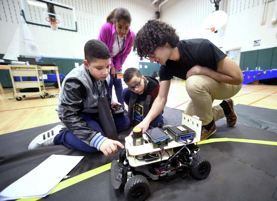 Left to right, Persio Anthony Veras, 11, Maria Gutierrez, 12, and Jeciel Jandel Suarez Valcarcel, 12, of Fair Haven School listen to Yale University students Omid Rooholfada talk about the unhackable self-driving car being developed by Y-Driving, a segment of the Flint Research Group, during a Code Haven Project Fair at Bishop Woods School in New Haven on April 27, 2018. Photo: Arnold Gold / Hearst Connecticut Media / New Haven Register