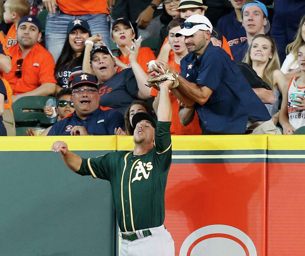 PHOTOS: More shots of fan interfering with Max Stassi's home run ball HOUSTON, TX - APRIL 29: Stephen Piscotty #25 of the Oakland Athletics leaps for a ball hit by Max Stassi #12 of the Houston Astros in the fifth inning but is interfered with by a fan at Minute Maid Park on April 29, 2018 in Houston, Texas. Umpires reviewed and upheld that Stassi was out.