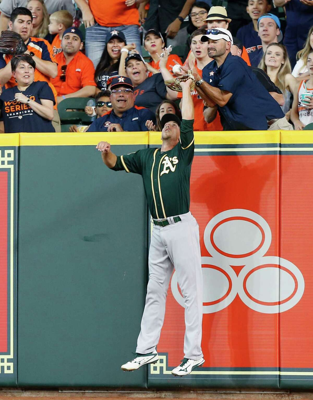 HOUSTON, TX - APRIL 29: Stephen Piscotty #25 of the Oakland Athletics leaps for a ball hit by Max Stassi #12 of the Houston Astros in the fifth inning but is interfered with by a fan at Minute Maid Park on April 29, 2018 in Houston, Texas. Umpires reviewed and upheld that Stassi was out.