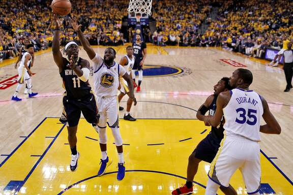 Jrue Holiday (11) puts up a shot defended by Draymond Green (23) in the first half as the Golden State Warriors played the New Orleans Pelicans in Game 1 of the second round of the Western Conference Finals at Oracle Arena in Oakland, Calif., on Saturday, April 28, 2018.