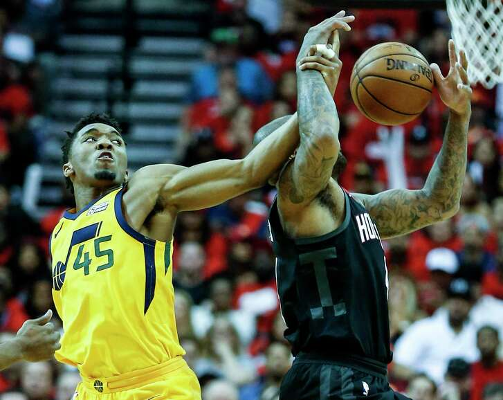 Utah Jazz guard Donovan Mitchell (45) and Houston Rockets forward PJ Tucker (4) fight for a loose ball, that Tucker ended up taking away from Mitfchell, during the second half in Game 1 of an NBA basketball second-round playoff series at Toyota Center on Sunday, April 29, 2018, in Houston.