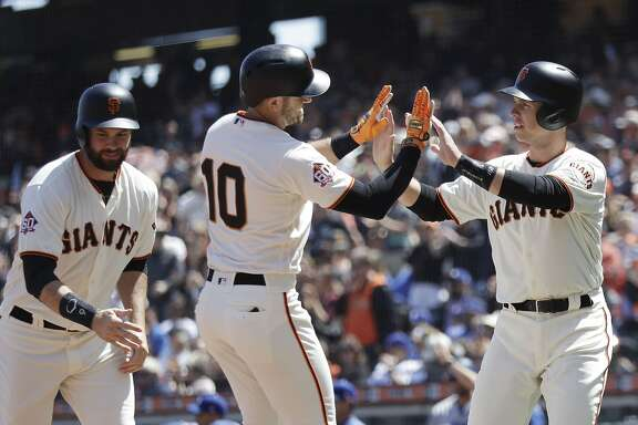 San Francisco Giants' Evan Longoria (10) is met at the plate after driving in Buster Posey, right, and Brandon Belt, left, with a three-run home run during the first inning of a baseball game against the Los Angeles Dodgers, Sunday, April 29, 2018, in San Francisco. (AP Photo/Marcio Jose Sanchez)