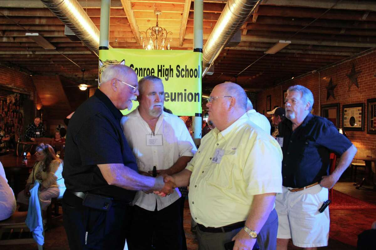 """The Vietnam War, a Little League game, and the basketball team's run at the state tournament were just a few memories shared by Conroe High School class of 1968 classmates at the 50th reunion on Saturday at Martin's Hall in downtown Conroe. Tom Whitesides and Reggie Coe shake hands next to Peyton """"Herkey"""" Mullins and Leslie Moses."""