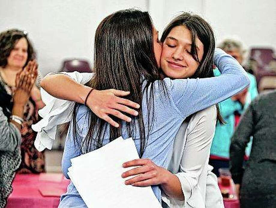 Olivia Weeks (right) gets a hug from her mother, Tabitha Weeks, after she read her essay that she wrote to get accepted into Harvard University during the Decatur Correctional Center Volunteer Luncheon and Program in Decatur. Before her mother went to prison in 2012 for an aggravated DUI that caused a death, Olivia was a competent student but not an outstanding one, certainly not one on track for an Ivy League education. When her mother left, Olivia, then 12 years old, made a choice to excel. Photo:       Clay Jackson | Herald & Review (AP)