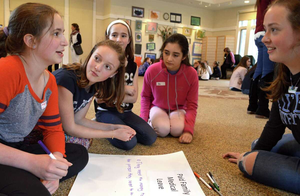 Mentor Alexandra Gillespie, 15, of New Canaan, at right, facilitates a discussion on paid family medical leave at the local nonprofit LiveGirl's leadership summit