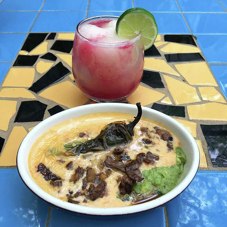 Chile toreado queso with bistek, jalapeño and guacamole and a frozen margarita with a prickly pear swirl from La Fonda on Main
