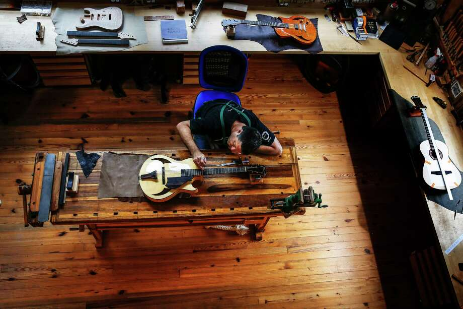 Stephen Marchione, owner of Marchione Guitars, works on a nearly finished guitar out of his shop in the Montrose area. His high-end guitar shop makes about 50 of the instruments every year. Photo: Michael Ciaglo, Staff / © 2016  Houston Chronicle