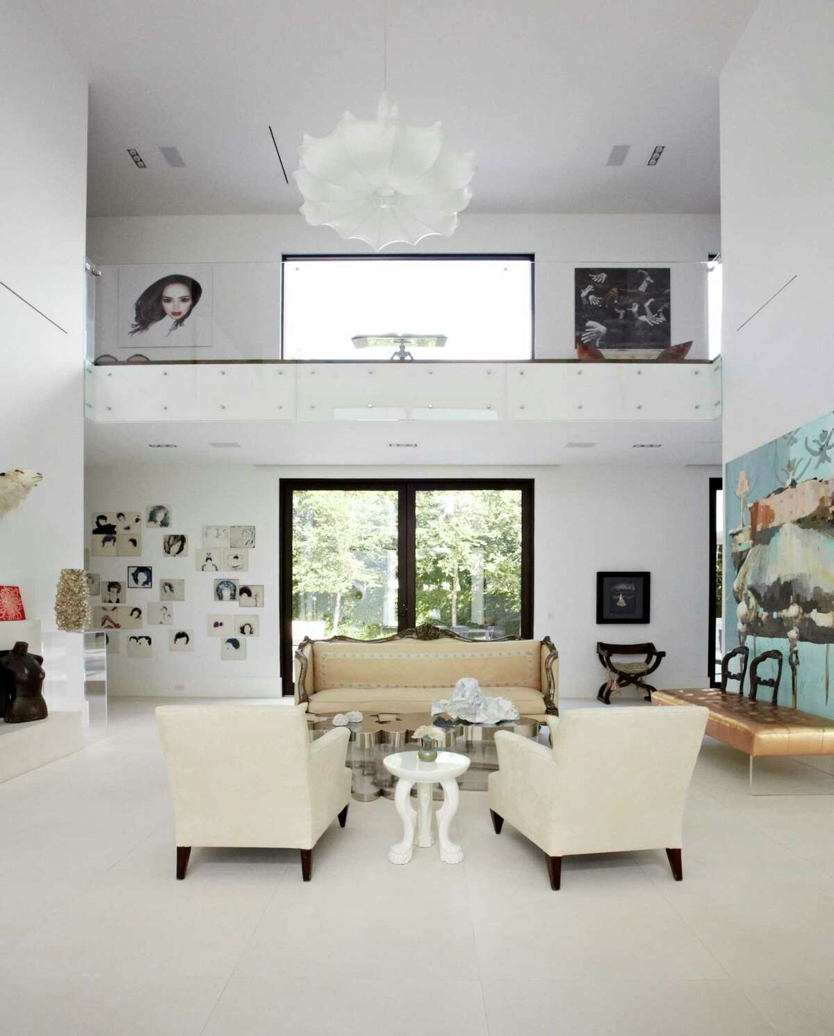 A simple backdrop of white walls and furniture provides a blank canvas for the couple's art collection. Lucinda is the owner of Lucinda Loya Interiors; Javier is CEO of OTC Global Holdings.