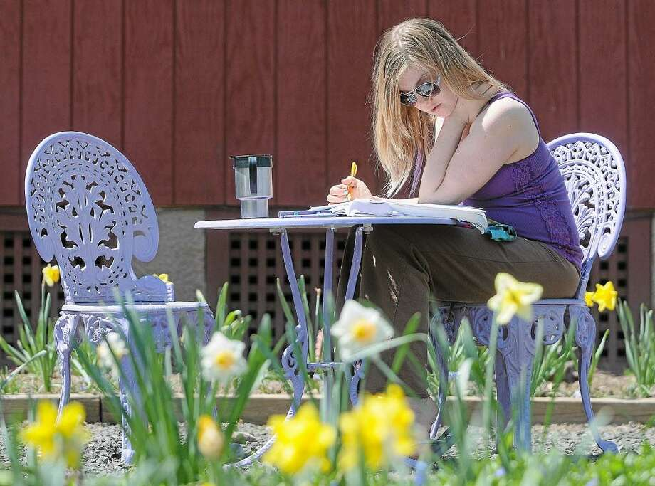 A Middlesex Community College student finishes a math assignment outdoors. Photo: File Photo / TheMiddletownPress