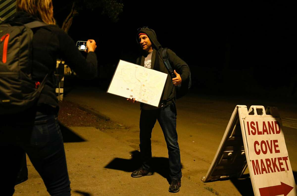 San Francisco Chronicle reporter Heather Knight takes a photo of fellow reporter Peter Hartlaub while he holds a map before boarding the 25-Treasure Island at 3:12 a.m. during the Total Muni 2018 challenge, an attempt to ride every Muni line in one day in San Francisco, Calif. Monday, April 30th, 2018.