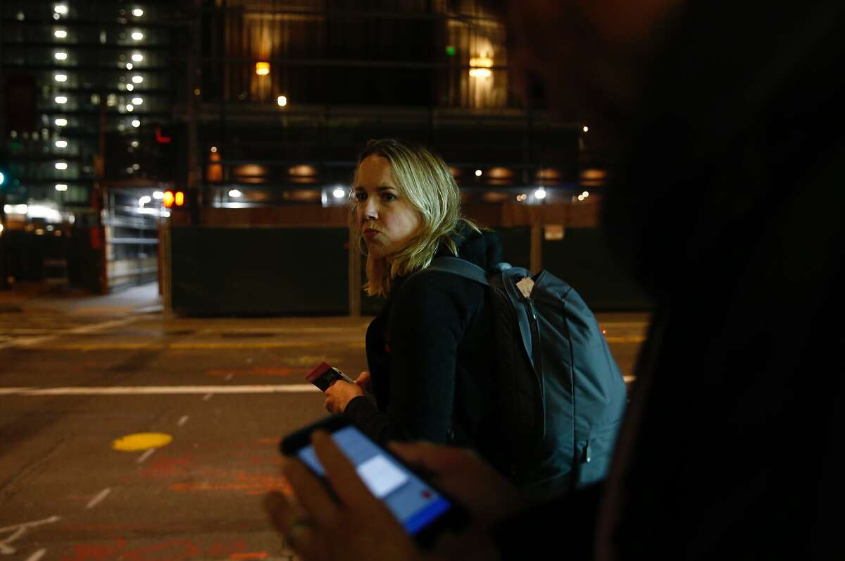 San Francisco Chronicle reporter Heather Knight looks for a 38-Geary bus while Peter Hartlaub checks a map on his phone around 3:35 a.m. during the Total Muni 2018 challenge, an attempt to ride every Muni line in one day in San Francisco, Calif. Monday, April 30th, 2018.