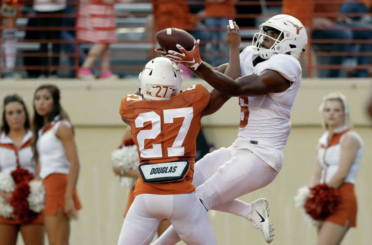 Texas defensive back Donovan Duvernay (27) breaks up a pass intended for wide receiver Devin Duvernay, right, during the team's Orange-White intrasquad spring college football game, Saturday, April 21, 2018, in Austin, Texas. (AP Photo/Eric Gay)