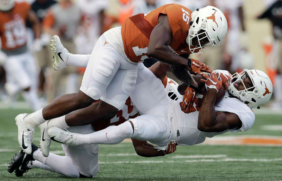 Texas wide receiver Devin Duvernay, right, is hit by defensive back Donovan Duvernay after making a catch for a first down during the team's Orange-White intrasquad spring college football game, Saturday, April 21, 2018, in Austin, Texas. (AP Photo/Eric Gay)