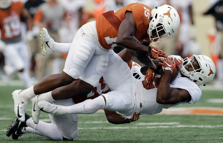 Texas wide receiver Devin Duvernay, right, is hit by defensive back Donovan Duvernay after making a catch for a first down during the team's Orange-White intrasquad spring college football game, Saturday, April 21, 2018, in Austin, Texas. (AP Photo/Eric Gay) Photo: Eric Gay, Associated Press / Copyright 2018 The Associated Press. All rights reserved.