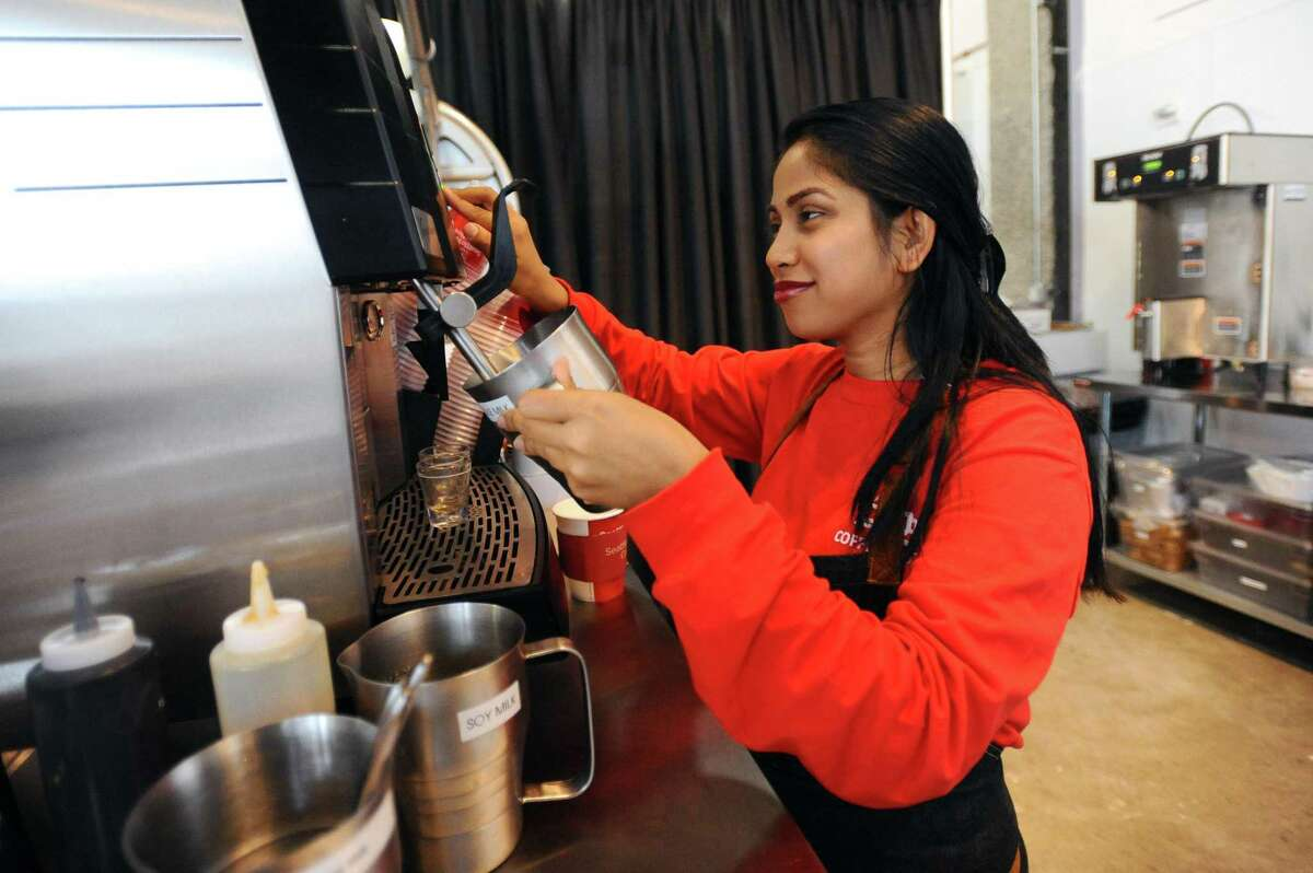 Barista Ferdous Ara makes a latte inside the new coffee shop Coffee Spot, at 24 Harbor Point Road, in Stamford, Conn., on Wednesday, April 25, 2018.