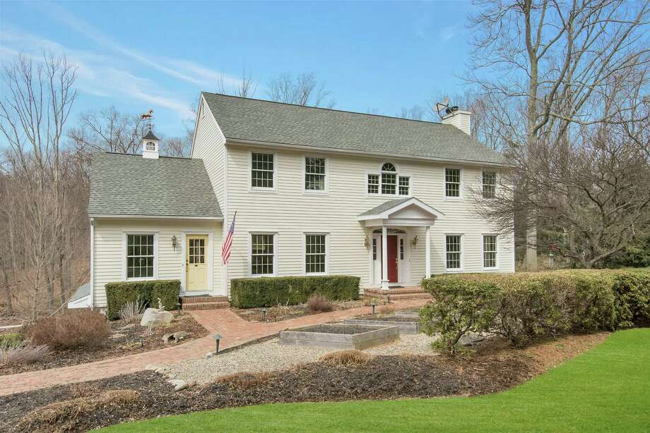 The pale yellow, nine-room colonial house at 23 Long Lots Road sits on a rear lot.