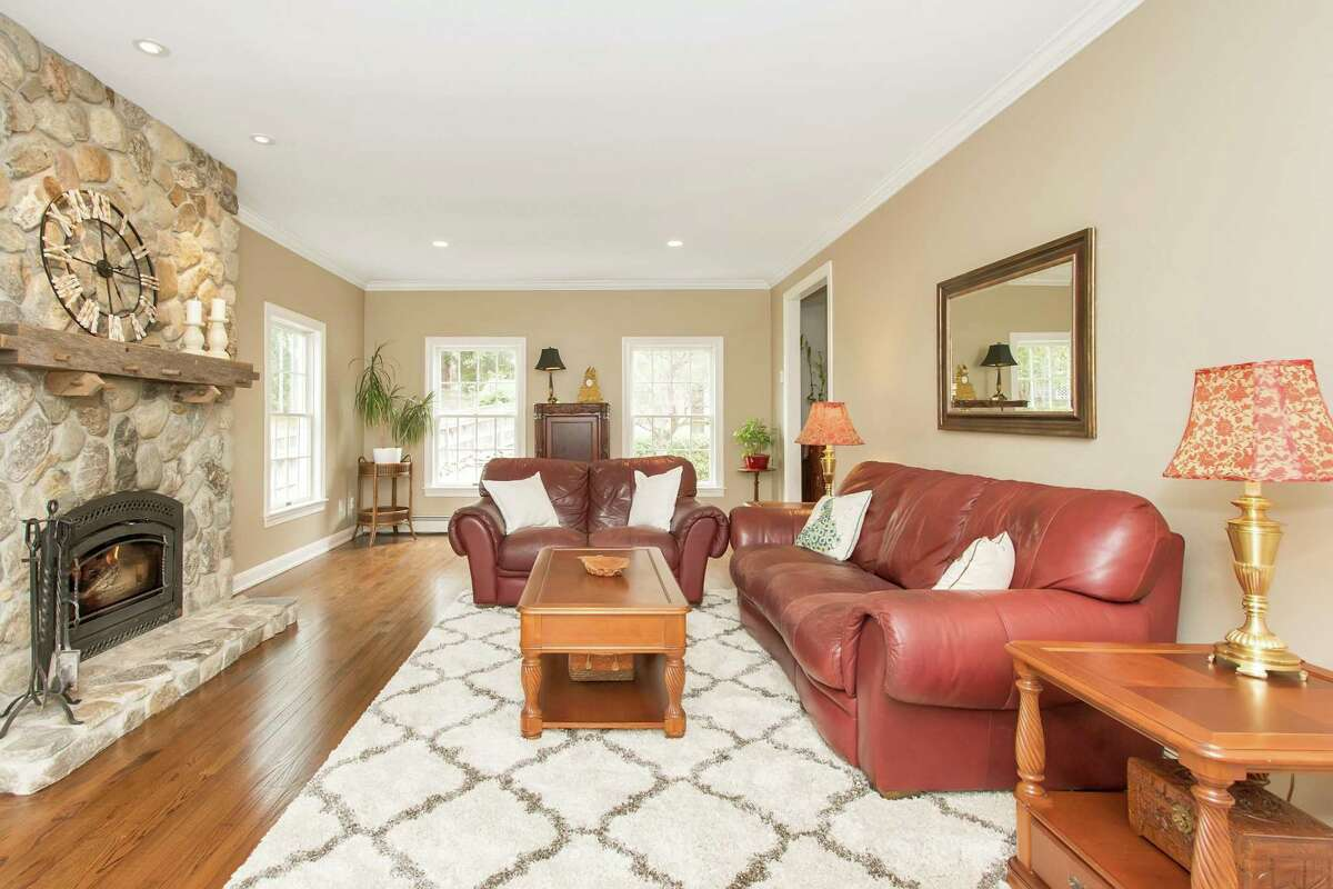 The formal living room features a wood-burning, floor-to-ceiling fieldstone fireplace with a hand-hewn wood beam mantel and French doors to the sizable, two-level, wrap-around wood deck.