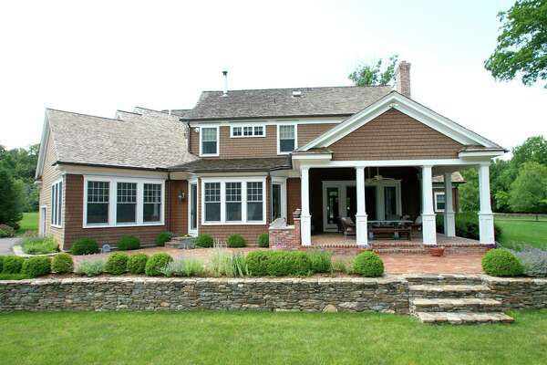 The Cape Cod Brown-colored custom-built colonial house at 99 Burrwood Common has a covered red brick patio or porch and a stone wall to a large yard with room for a pool.