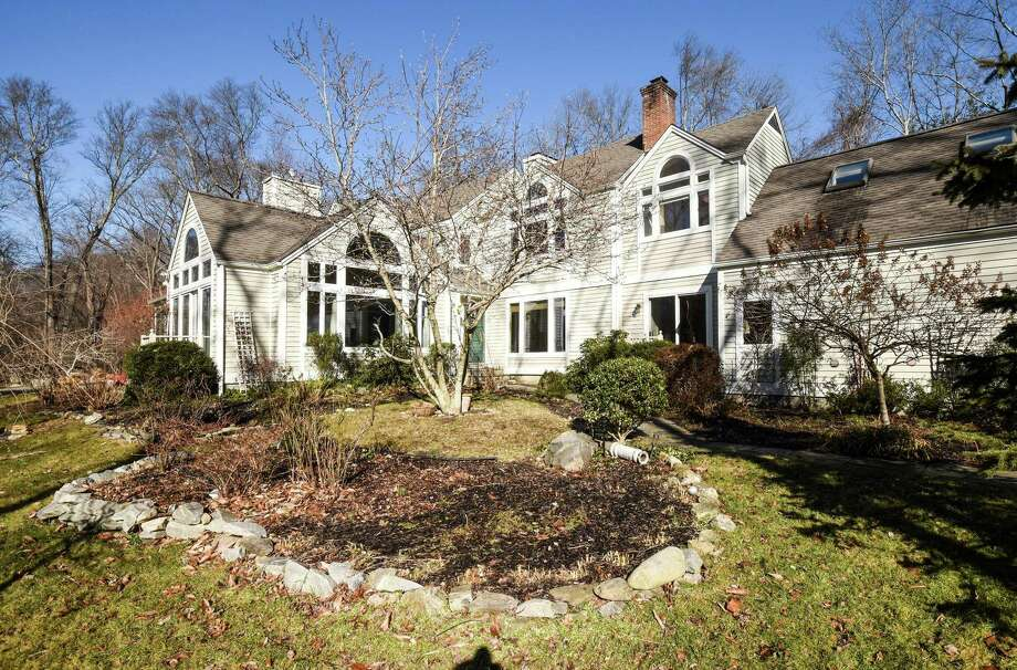 The pale gray colonial contemporary house at 90 Nursery Road sits on a 1.18-acre level parcel located along the Five Mile River.