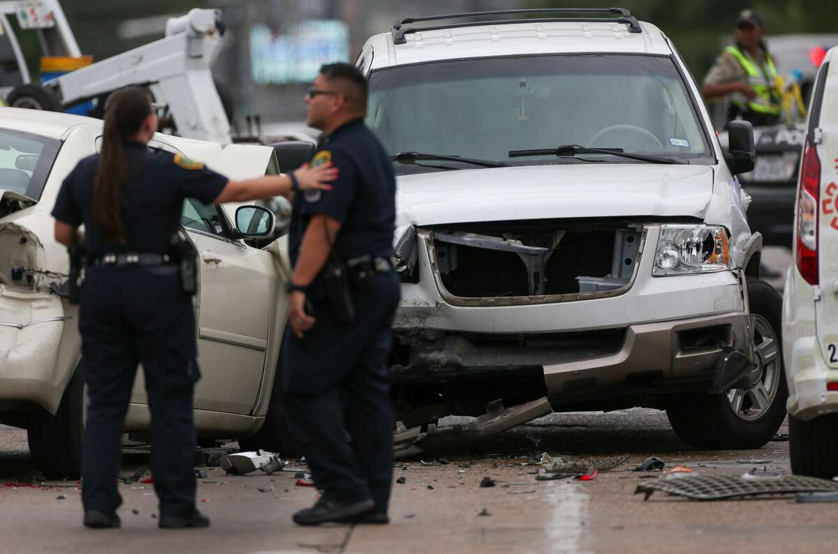 Houston Police officers investigate the scene of a multiple-vehicle crash on the intersection of Hillcroft Avenue and Westheimer Road Monday, April 30, 2018, in Houston. A woman died during the crash. ( Godofredo A. Vasquez / Houston Chronicle )