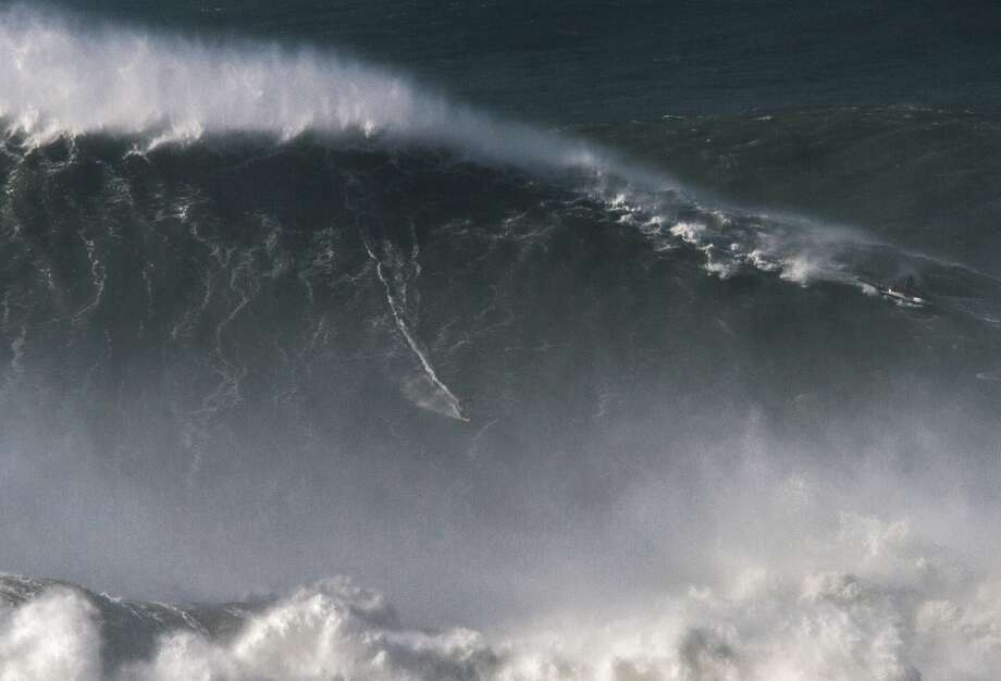 In this photo taken Nov. 8 2017, Brazilian surfer Rodrigo Koxa rides what has been judged the biggest wave ever surfed, at the Praia do Norte, or North beach, in Nazare, Portugal. On Saturday, April 28 2018, the World Surf League credited Koxa with a world record for riding the biggest wave ever surfed and said that its judging panel determined the wave was 80 feet (24.38 meters).  Photo: Pedro Cruz, Associated Press
