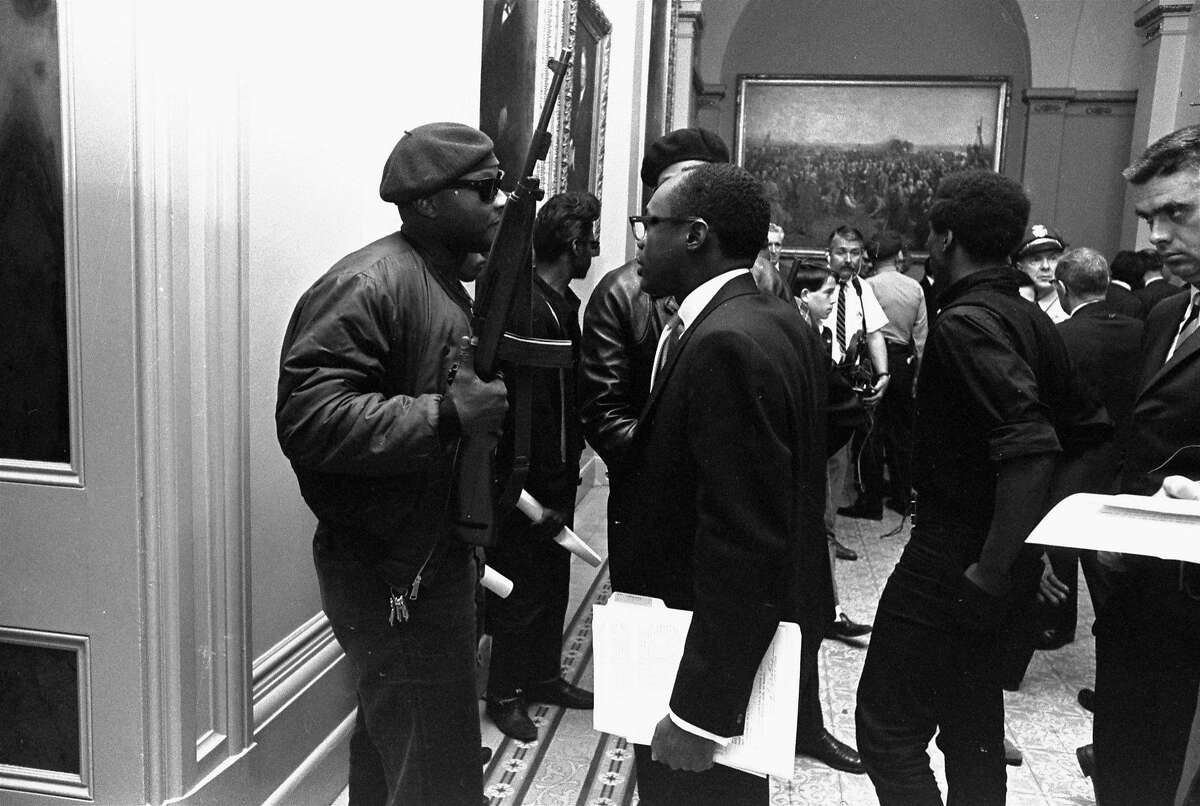 Then-Assemblyman Willie L. Brown Jr., D-San Francisco, center, talks to a Black Panther Party member May 3, 1967. They were protesting a bill before an Assembly committee restricting the carrying of loaded weapons in public.