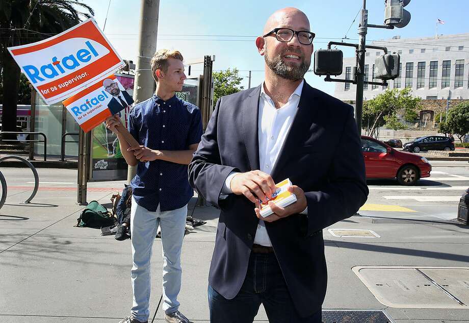 District 8 supervisor candidate Rafael Mandelman (middle) watches for voters as volunteer Scott Cartlson (left) holds a sign on Market at Dolores streets on Monday, April 23, 2018, in San Francisco, Calif. Photo: Liz Hafalia / The Chronicle